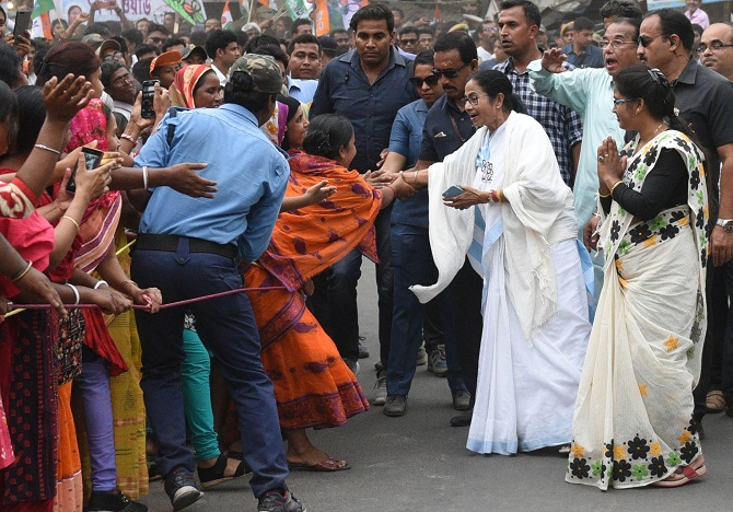 TMC supremo and Chief Minister Mamata Banerjee shake hand with her supporters during a road show in Shantipur. Photograph: ANI Photo