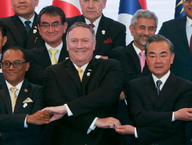 U.S. Secretary of State Mike Pompeo crosses his arms for the traditional ASEAN handshake with Chinese Foreign Minister Wang Yi and other fellow diplomats during the 26th ASEAN Regional Forum (ARF) in Bangkok