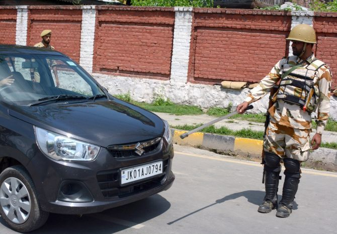 A security person stops a vehicle for checking in Srinagar.