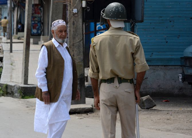 An elderly man seeks permission to go forward amid curfew in Srinagar.
