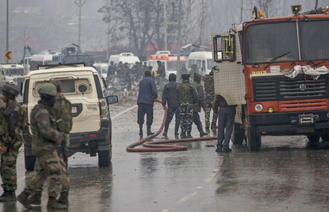 Firemen spray water to wash away blood stains at the site of the suicide bomb attack at Lathepora Awantipora in south Kashmir's Pulwama district, February 14, 2019. Photograph: PTI Photo
