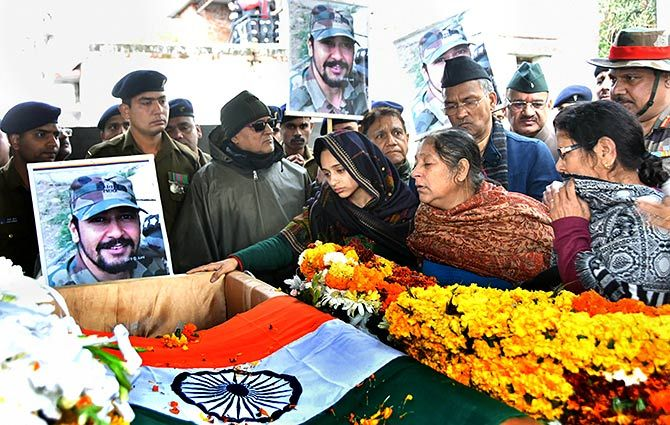 Major Vibhuti Shankar Dhaundiyal's wife Nitika Kaul and family members pay homage to the brave soldier who lost his life in the February 18 encounter with terrorists in Dehradun. Photograph: PTI Photo