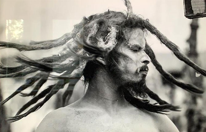 A sadhu swings his dreadlocks after a bath at the ghat