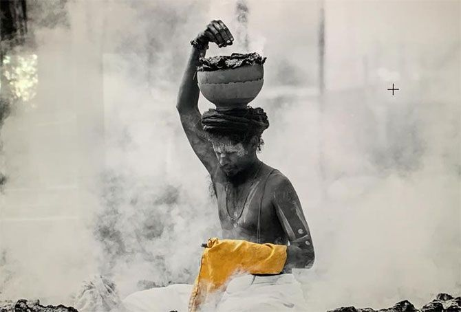 A sadhu surrounded by smoke from burning cow dung cakes