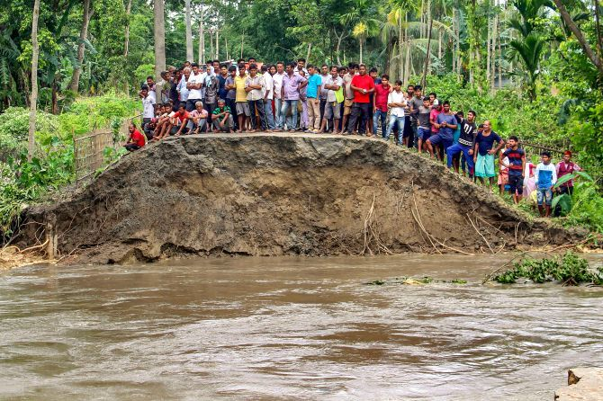 People stand on a damaged embarkment washed out by the floods due to incessant rainfalls, at Hajo in Kamrup