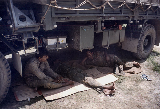 Fatigued soldiers take a rest under a truck during the War. Rediff Archives
