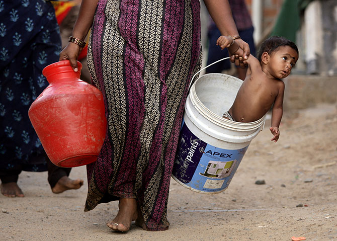 A woman carries her son in a bucket after collecting water from a municipal water tanker on the outskirts of Chennai. Photograph: P Ravikumar/Reuters.