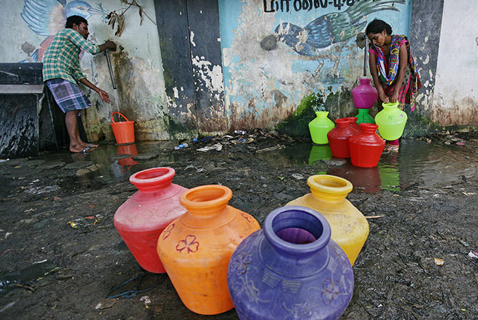 Residents fill their empty containers with water from a municipal tap in Chennai. Photograph: P Ravikumar/Reuters.