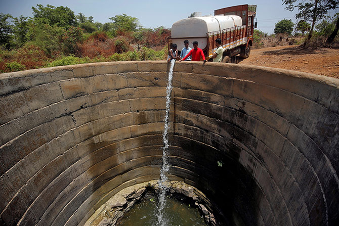 A dried-up well is refilled with water from a water tanker in Thane district in the western state of Maharashtra. Photograph: Francis Mascarenhas/Reuters.