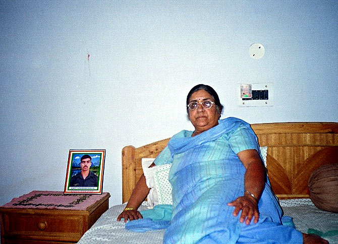 Captain Saurabh Kalia's mother with his picture by her bedside