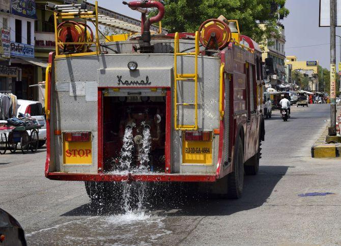 A fire brigade vehicle waters a road in Churu. Photograph: PTI Photo