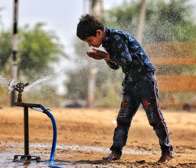 A young boy stands next to a leaking water source in Churu. Photograph: PTI Photo