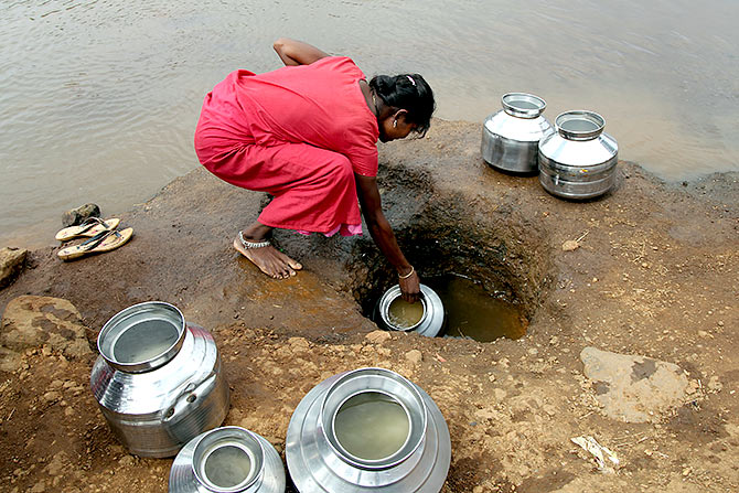 A woman fetches water from an opening made to filter water next to a polluted lake in Maharashtra's Thane district. Photograph: Prashant Waydande/Reuters