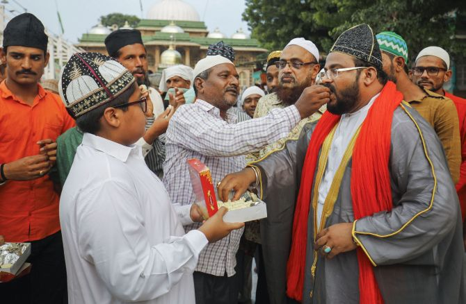 Muslims offer each other sweets after the verdict outside the Shah-e-alam shrine in Ahmedabad. Photograph: PTI Photo