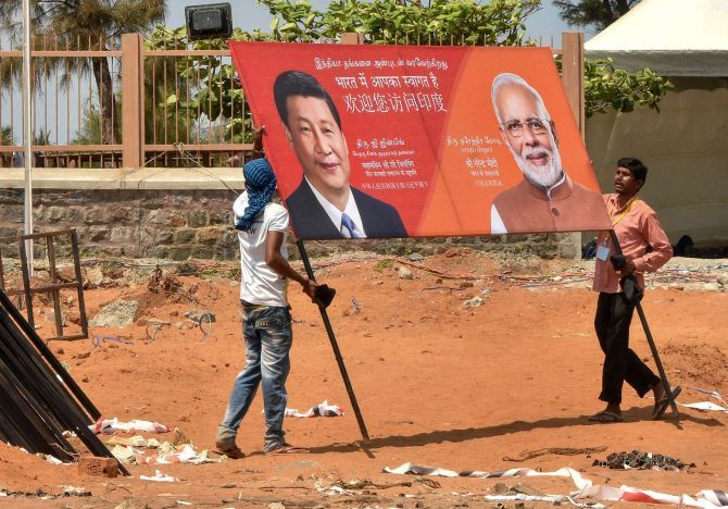 Workers carry a hoarding welcoming Prime Minister Narendra Damodardas Modi and Chinese President Xi Jinping in Mahabalipuram. Photograph: PTI Photo