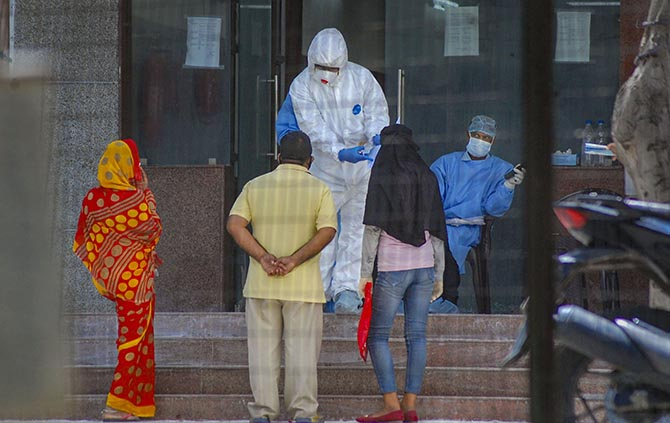 Medics attend to people arriving for COVID-19 tests at the Hallet Hospital in Kanpur. Photograph: PTI Photo