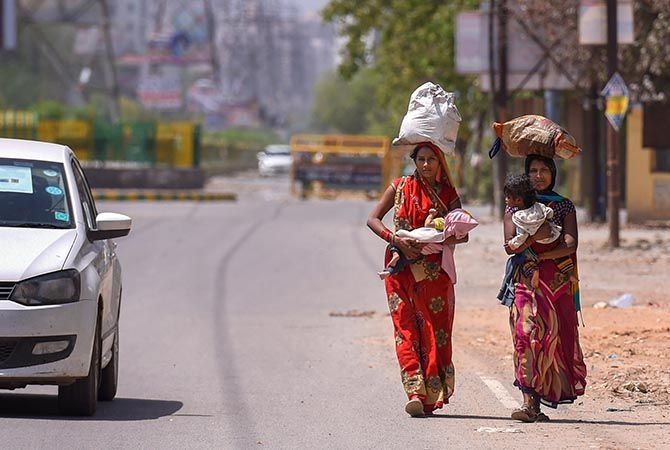 Women carrying their babies and essential items walk on a nearly-deserted street in Ghaziabad, April 7, 2020. Photograph: Atul Yadav/PTI Photo