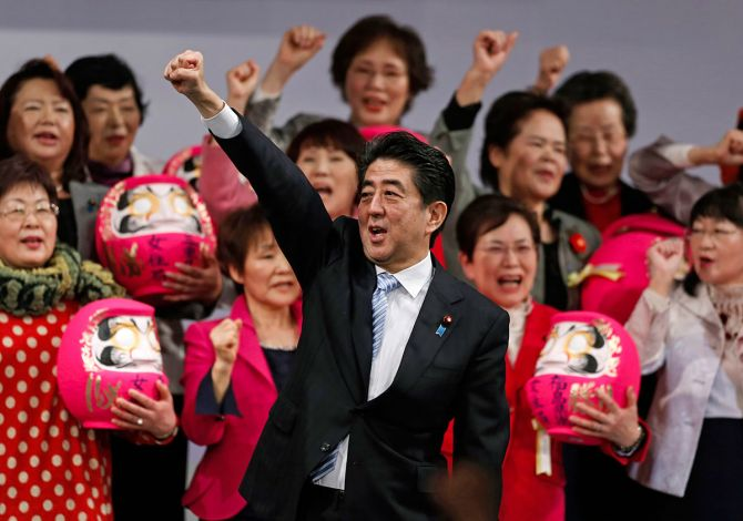 Prime Minister Abe Shinzo raises his fist with members of the ruling Liberal Democratic Party holding Daruma dolls, which are believed to bring good luck, during the annual party convention in Tokyo, March 8, 2015. Photograph: Yuya Shino/Reuters