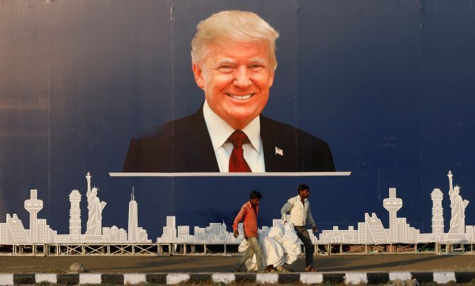 Workers walk past a hoarding of United States President Donald J Trump ahead of his visit to Ahmedabad, February 22, 2020. Photograph: Anushree Fadnavis/Reuters