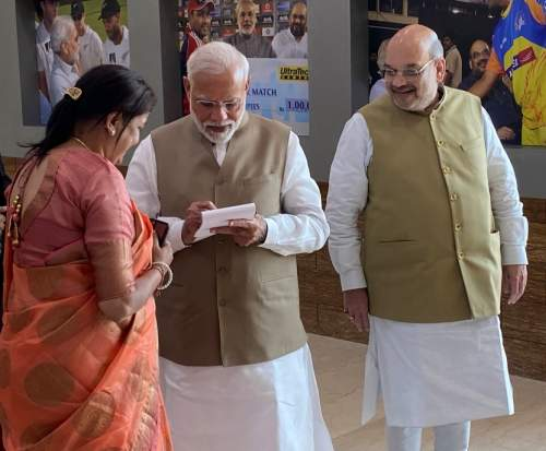 Prime Minister Narendra Damodardas Modi scribbles a message for Sonalben Shah as her husband wearing a big smile watches at the Motera stadium, February 24, 2020.