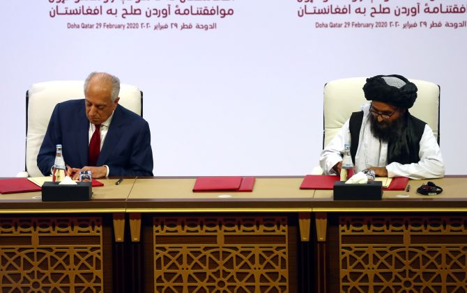 Mullah Abdul Ghani Baradar, leader of the Taliban delegation, and Zalmay Khalilzad, the US envoy for peace in Afghanistan, sign the agreement at a ceremony in Doha, Qatar, February 29, 2020. Photograph: Ibraheem al Omari/Reuters