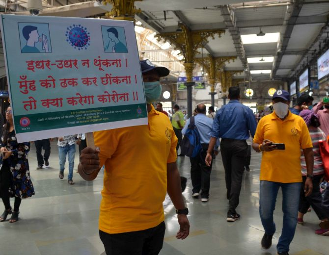 A volunteer holds a placard to create awareness about COVID-19 at the Chhatrapati Shivaji Maharaj Terminus in Mumbai. Photograph: Sahil Salvi