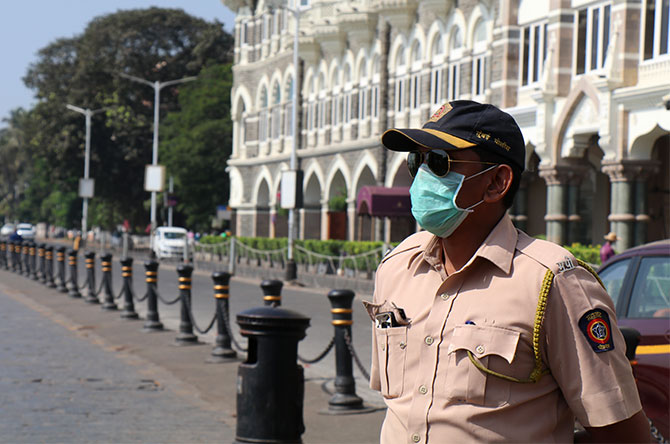 A cop is seen wearing mask as a precaution at Gateway of India