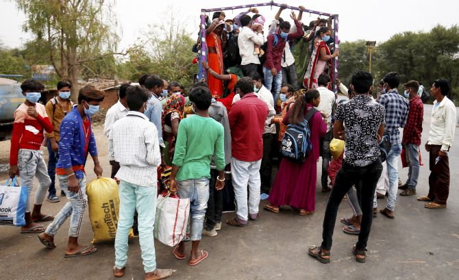 Indians and their families board a truck in Ahmedabad to return to their villages