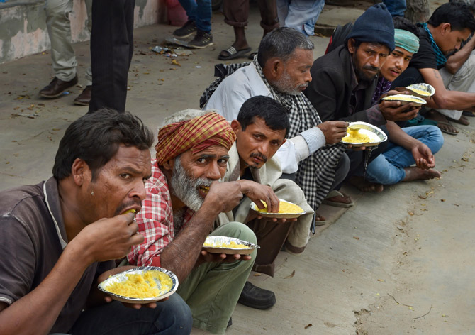 Homeless Indians and daily wagers eat food at a government shelter near the Nigam Bodh ghat in New Delhi, March 26, 2020. Photograph: Manvender Vashist/PTI Photo