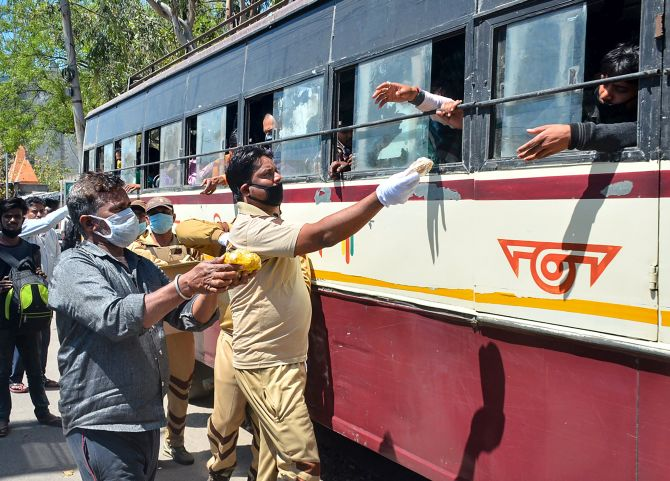 Volunteers provide meals to Indians heading to their villages inside a bus in Moradabad, March 28, 2020. Photograph: PTI Photo