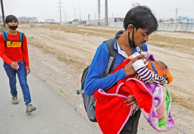 An Indian feeds his newborn baby as he walks on a highway looking out for transport to return to his village