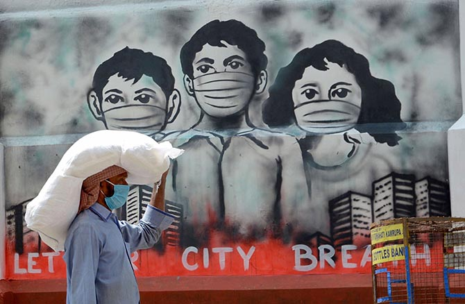 A labourer in Guwahati walks past a mural during the nationwide lockdown