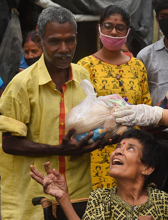 A visually challenged person in Kolkata receives a relief packet from volunteers during the ongoing COVID-19 lockdown.