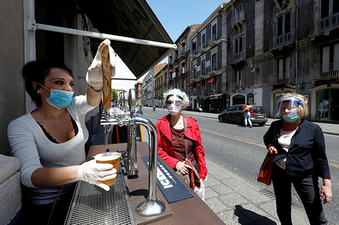 #A woman wearing a face mask pours beer from a tap as Italy begins a staged end to a nationwide lockdown due to the spread of the coronavirus disease in Catania, Italy.