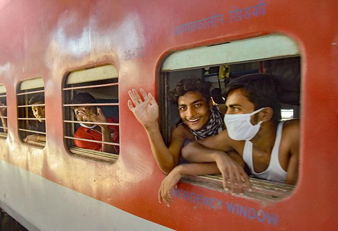 Migrants from Bihar wave as they board a special train to Patna