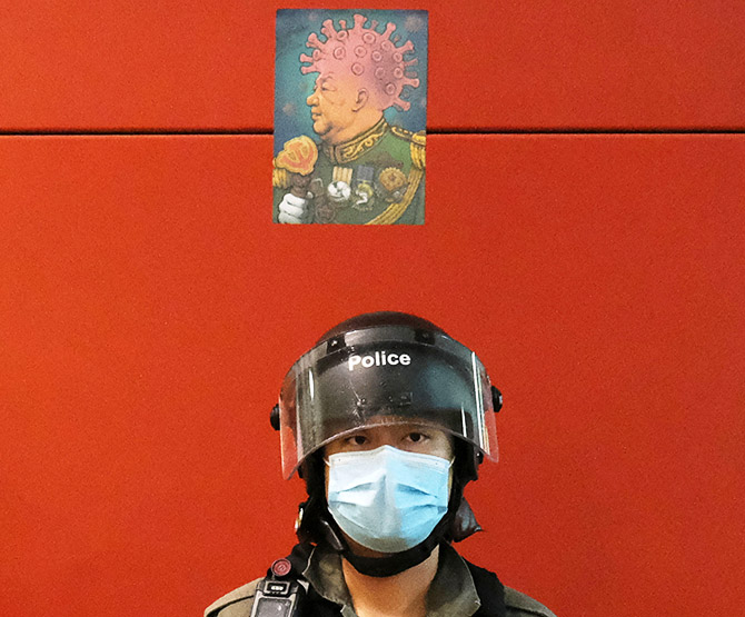 A defaced picture mocking Chinese President Xi Jinping and the coronavirus disease is seen above a riot policeman's head in Hong Kong, April 26, 2020. Photograph: Tyrone Siu/Reuters