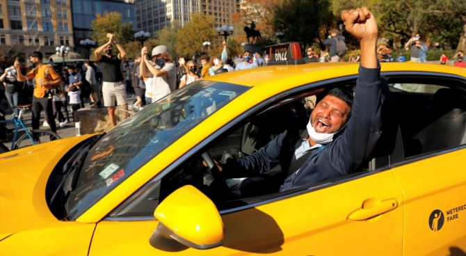 A New York cabbie celebrates Joe Biden's victory at Union Square, New York City. Photograph: Andrew Kelly/Reuters