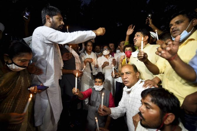 Congress activists participate in a candle light protest over the death of the Hathras gangrape victim, at Safdarjung hospital in New Delhi
