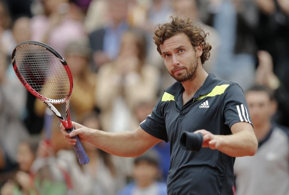 Ernests Gulbis of Latvia reacts after winning his men's singles match against Roger Federer