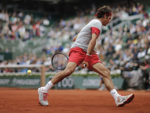 Roger Federer of Switzerland returns the ball to Ernests Gulbis of Latvia