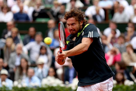Ernests Gulbis of Latvia returns a shot in his men's singles match against Roger Federer
