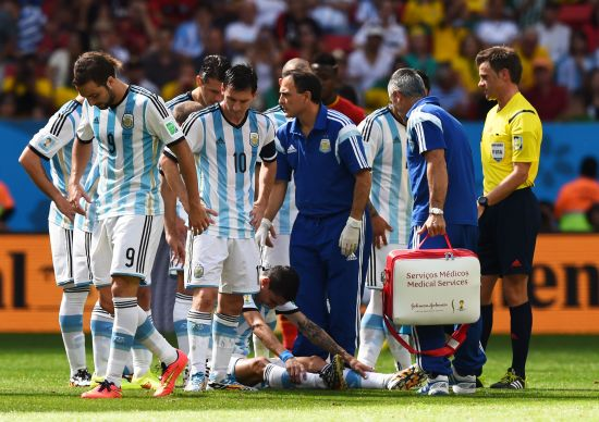 Angel di Maria of Argentina receives treatment as his teammates look on
