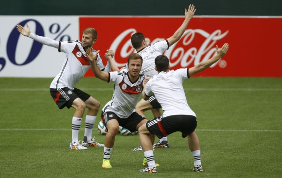 Germany's national soccer players Christoph Kramer (L), Mario Goetze (2nd L) and teammates warm up during a training session