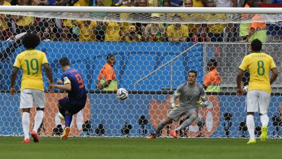 Robin van Persie of the Netherlands (2nd L) shoots to score his penalty past Brazil's Julio Cesar