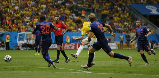 Brazil's Oscar (C) attempts a shot against the Netherlands
