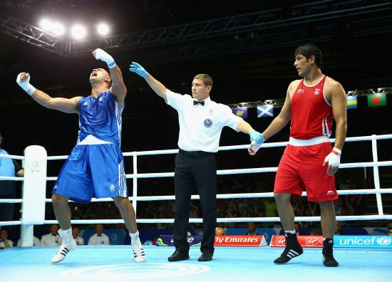 Ross Henderson of Scotland (blue) celebrates victory over Parveen Parveen Kumar of India in the Men's Super Heavy +91kg preliminaries at Scottish Exhibition And Conference Centre during day two of the Glasgow 2014 Commonwealth Games