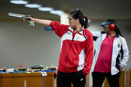 Shun Xie Tao of Singapore and Malaika Goel of India compete in the womens 10 meter air pistol
