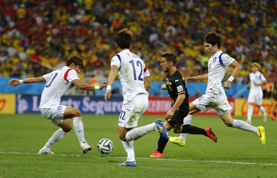 Belgium's Kevin Mirallas fights for the ball with South Korea's Hong Jeong-ho (left), Lee Yong and Han Kook-young (right)