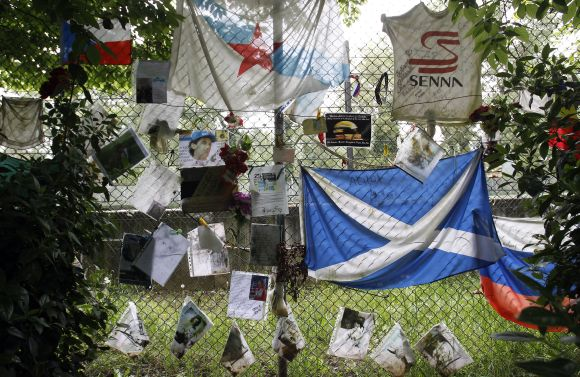 Handwritten notes and flags left by fans are pictured near the memorial statue of Brazilian Formula One driver Ayrton Senna at the race track in Imola