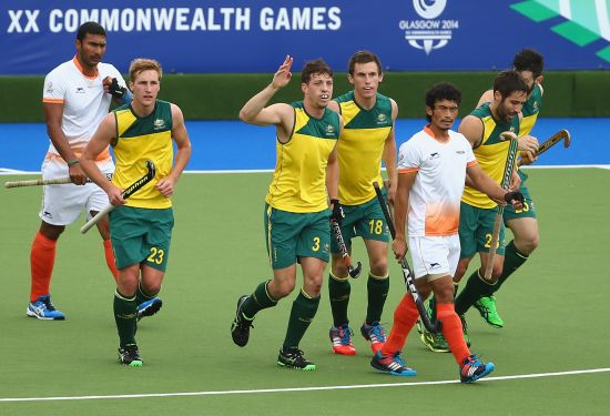 Simon Orchid (centre) of Australia celebrates after scoring a goal during the men's preliminaries match between India and Australia at the Glasgow National Hockey Centre